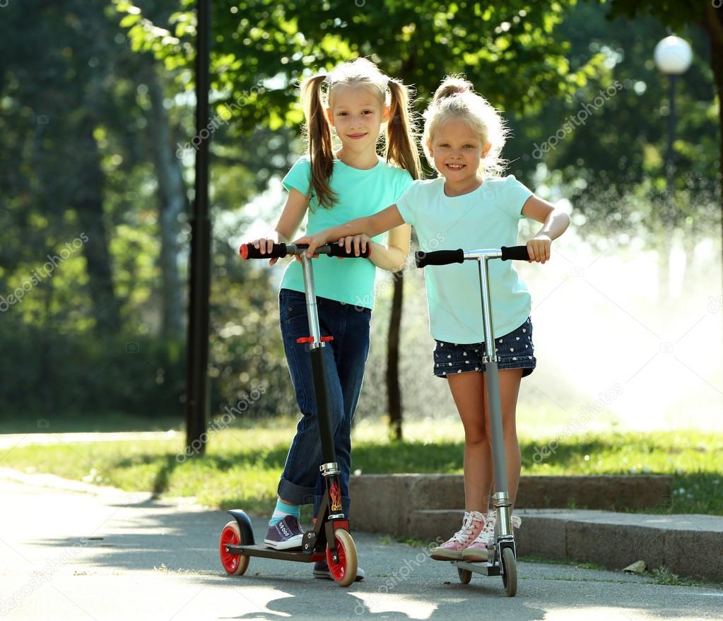 malé dívky Malé dívky, jízda na skútrech v parku — Fotografie od belchonock