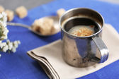 Metal cup of flavored coffee with lump sugar and flowers on table with napkin, closeup — Stock Photo