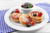 Fritters of cottage cheese with berries in plate on table, closeup — Stock Photo