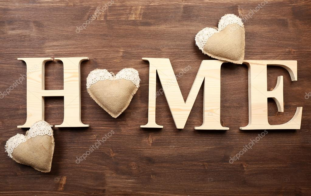 decorative letters forming word home with hearts on wooden background stock image