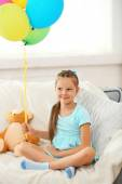 Beautiful little girl with teddy bear and colorful balloons sitting on sofa, on home interior background — Stock Photo