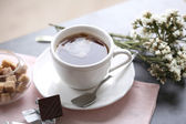 Cup of flavored coffee with chocolate on table with napkin, closeup — Stock Photo