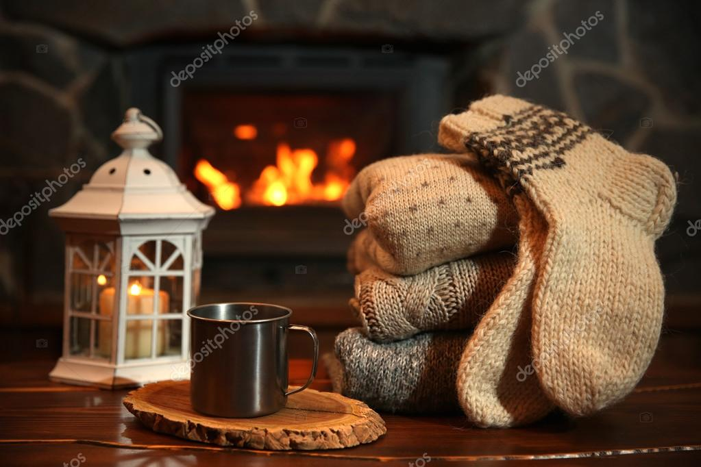 Fireplace Design fireplace background : Knitted clothes on table on fireplace background — Stock Photo ...