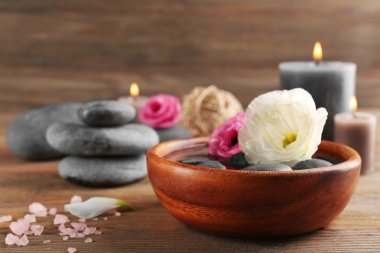 Beautiful composition of aroma candle with pebbles and flower in a bowl on wooden background