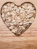 Oat cereal heart shaped on wooden surface. — Stock Photo