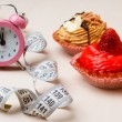 Sweet food measuring tape and clock on table — Stock Photo #74690363