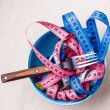 Many colorful measuring tapes in bowl on table — Stock Photo #75975141