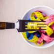 Many colorful measuring tapes in bowl on table — Stock Photo #76641581
