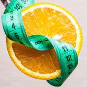 Green measuring tape and orange fruit — Stock Photo