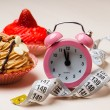 Sweet food measuring tape and clock on table — Stock Photo #77973328