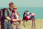 Couple backpacker tramping by seaside — Stock Photo