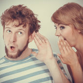 Woman telling an astonished man some secrets — Stock Photo