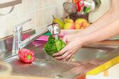 Woman washing fresh vegetables in kitchen — Stock Photo