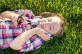 Very cheerful and funny little girl listening to music — Stock Photo