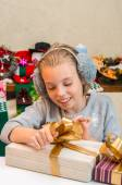 Little girl opens a box with a gift for Christmas. — Stock Photo
