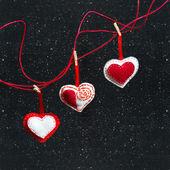 Drei Herzen aus Stoff auf einem schwarzen Hintergrund. Symbol der Liebe. — Stockfoto