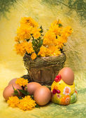 Eggs and spring flowers with a figure of a chicken — Stock Photo