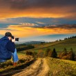 Man photographer in the mountains at sunset — Stock Photo #63801309