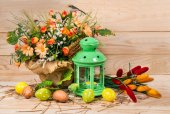 Easter decorated eggs and candlestick with spring flowers on a w — Stock Photo