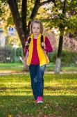 Pretty girl of school age in the autumn park. — Stock Photo