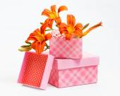 Decorative gift boxes with orange lily flowers — Stock Photo