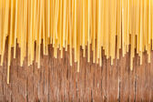Uncooked spaghetti posted on the a row  — Stock Photo
