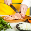 Cook knife cuts sausage — Stock Photo #62407739