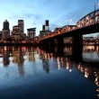 Downtown City Skyline of Portland Oregon along Willamette River with Hawthorne Bridge and Blue Hour Water Reflection Ripples at Night 1080p — Stock Video #62578245