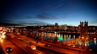 Panning Movie of Downtown City Skyline in Portland Oregon along Willamette River with Peak Hour Freeway Traffic and Blue Hour Water Reflection at Night 1080p — Stock Video