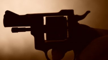 Silhouette of a mans hand with a handgun — Stock Video