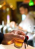 Uomo che tiene la chiave dell'automobile e vetro nel bar — Foto Stock