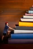 Climber climbs a heap of books — Stock Photo