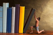 Man supporting falling book in the bookshelf — Stockfoto