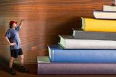 Climber climbs a heap of books — Stockfoto