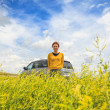 Happy woman with car among canola field — Stock Photo #52866317