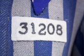 Number and symbol on nazi concentration camp clothes — Stock Photo