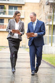 Two business people walking and discussing — Stock Photo