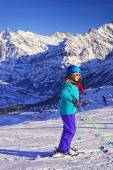 Young blond girl on ski at winter sport resort in swiss alps — Stock Photo