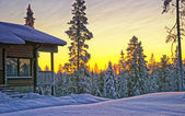 Wooden cottage house at winter sunset — Foto de Stock