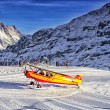 Yellow airplane landing to alpine resort in swiss alps in winte — Stok fotoğraf #59565753