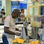 Black man extracting orange juice in cafe — Stock Photo #65933031