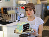Girl with creamy cake at the bakery  — Stock Photo