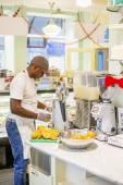 Black man extracting orange juice in cafe — Stock Photo