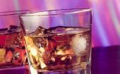 Whiskey glass on bar table with ice on warm atmosphere — Stock Photo