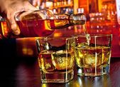 Barman pouring whiskey on bar table — Stock Photo