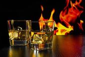 Glasses of whiskey with ice cubes in front of the flame — Stok fotoğraf