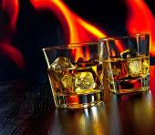 Two glasses of whiskey with ice cubes in front of the flame — Stok fotoğraf