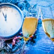 New Year or Christmas at midnight with champagne flutes with gold bubbles make cheers on blue light and clock — Stock Photo #52402859