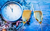 New Year or Christmas at midnight with champagne flutes with gold bubbles make cheers on blue light and clock — Stock Photo