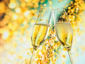 A pair of champagne flutes with golden bubbles on golden light background — Stock Photo